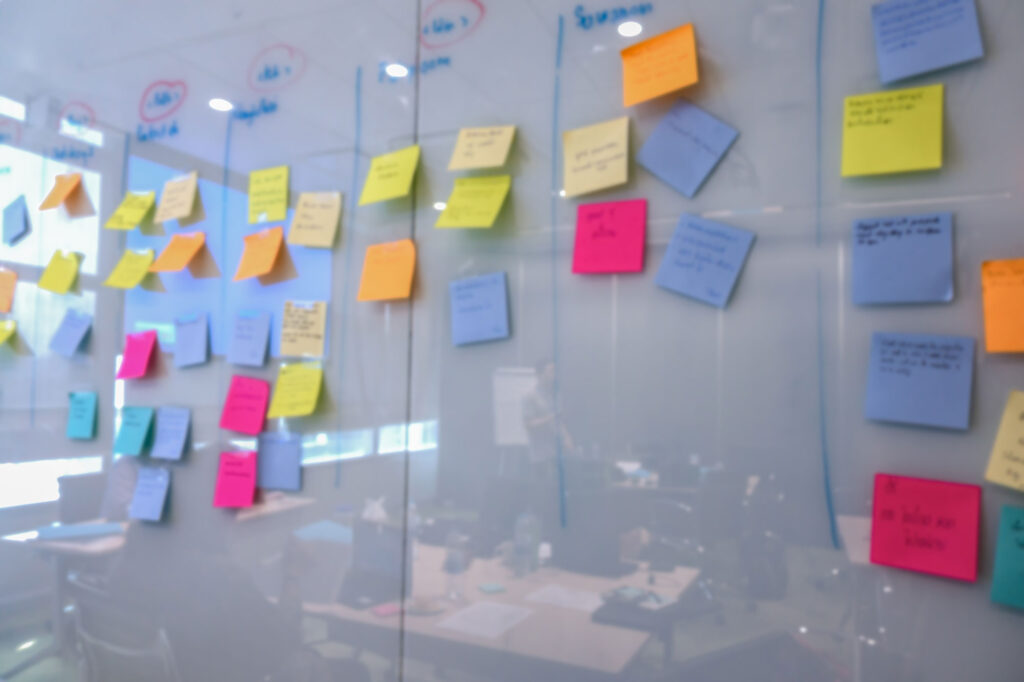 A glass board showing project planning in progress. It's covered with Post-its and wax pencil marks.