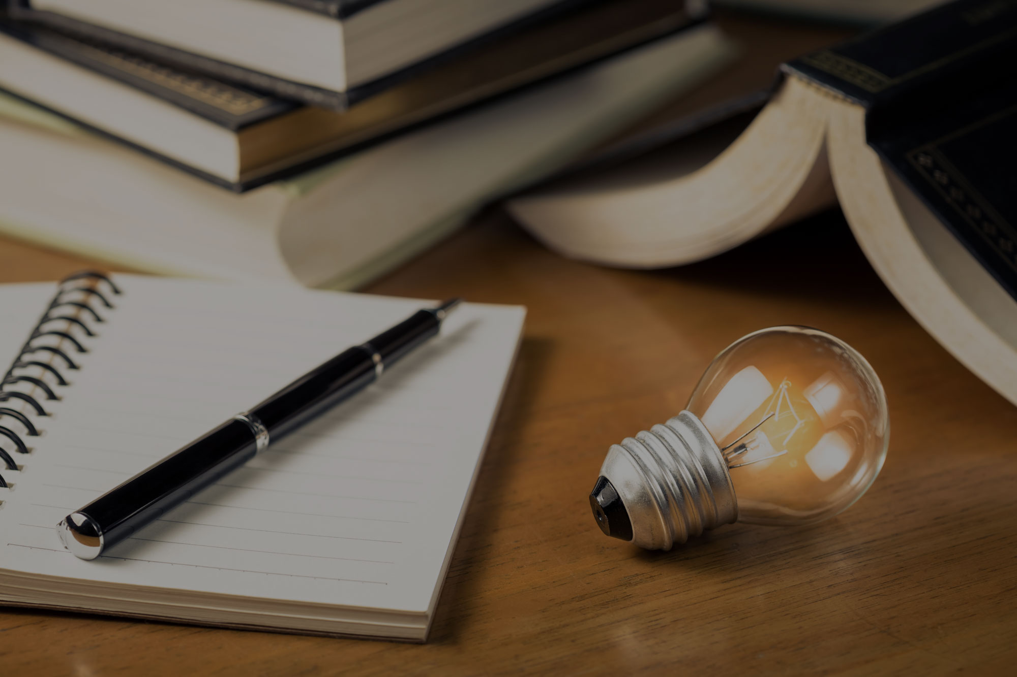An open notebook with an uncapped pen lying on it, ready for writing. To the right is a lit lightbulb.