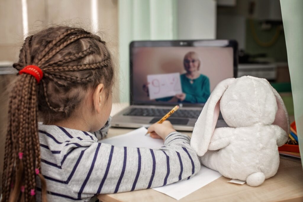 A girl engages in remote learning with her rabbit while a math teacher instructs on her computer screen