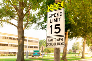 School speed limit sign with school building in background